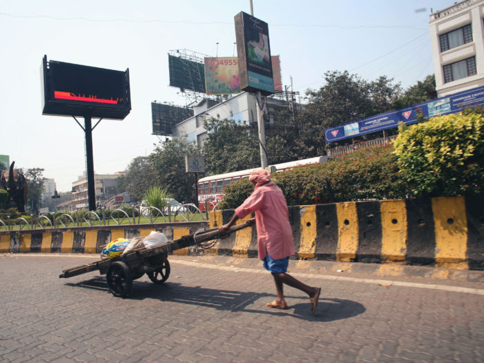 Travailleur qui pousse sa charette en plein Mumbai
